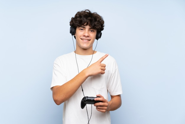 Young man playing with a video game controller over isolated blue wall pointing to the side to present a product