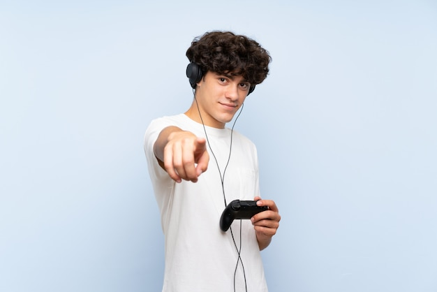 Young man playing with a video game controller over isolated blue wall points finger at you with a confident expression
