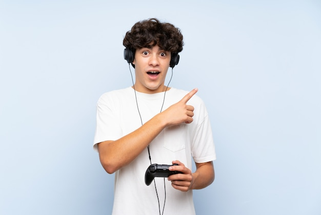 Young man playing with a video game controller over isolated blue wall surprised and pointing side