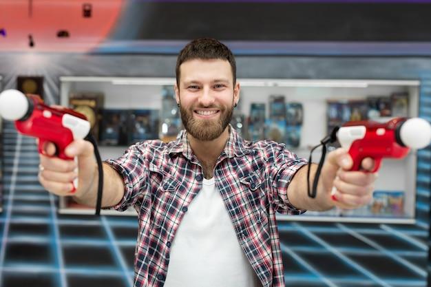 Молодой человек играет на приставке, эмоциональный геймер снимает игру с помощью контроллера оружия и улыбается.