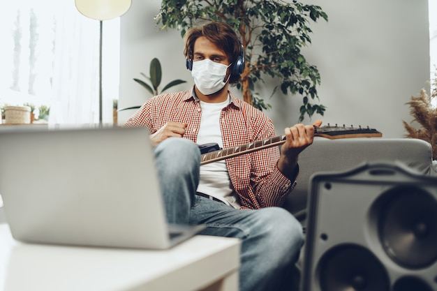 Young man plays guitar at home in medical mask. coronavirus quarantine lifestyle concept