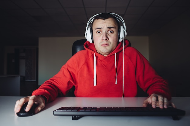 Young man plays a home game on his computer. gamer fear looking at your computer monitor
