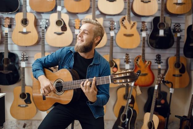 젊은 남자는 뮤직 스토어에서 어쿠스틱 기타에 재생됩니다. 악기 상점의 구색, 장비를 구입하는 남성 음악가