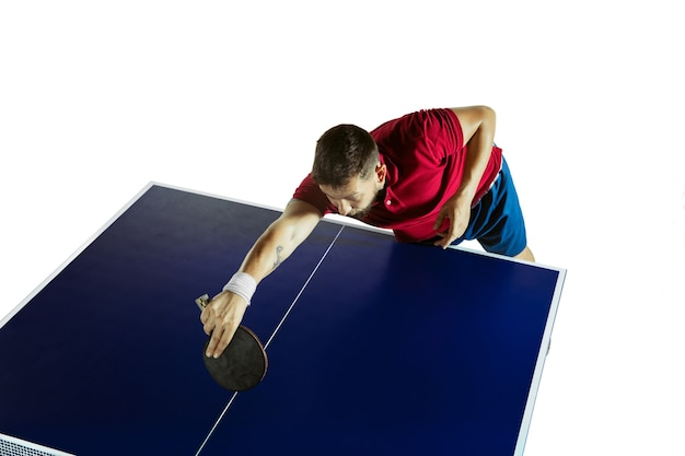 Young man plays ping pong on white wall.