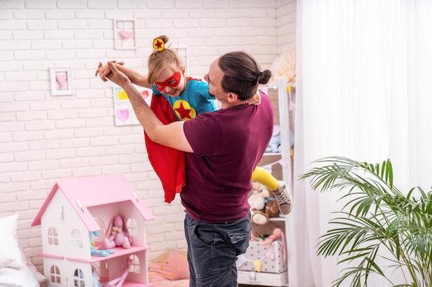 若い男が部屋でスーパーヒーローの娘と遊ぶ。