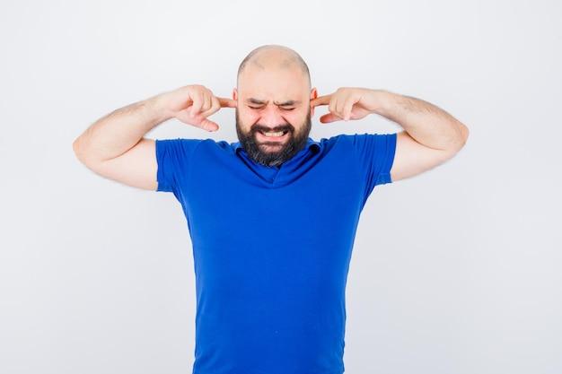 青いシャツに指で耳を塞いで緊張している若い男、正面図。