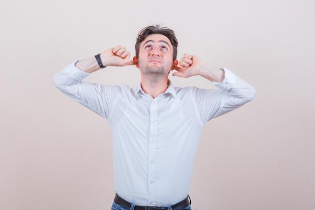 白いシャツに指で耳を差し込んでイライラしている若い男