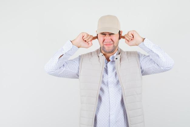 Giovane che collega le orecchie con le dita in camicia, giacca senza maniche, berretto e sembra stressante. vista frontale.
