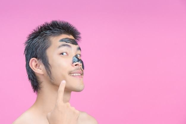 The young man pointed to the cheek without black cosmetics on his cheek and the pink .