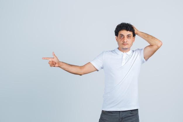 若い男は脇を向いて、白いtシャツ、ズボンを着て頭を抱え、物思いにふける。正面図。