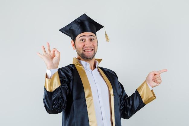 Giovane che indica da parte, mostrando il gesto giusto in uniforme laureato e che sembra allegro. vista frontale.