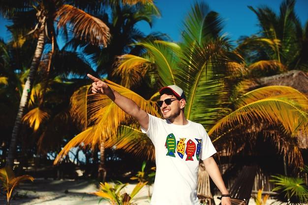 Молодой человек указывая в сторону во время прогулки на фоне пальм
