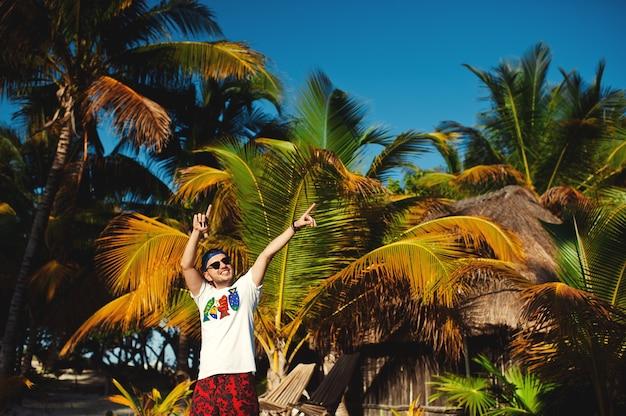 Молодой человек, указывая в сторону обеими руками на фоне пальм