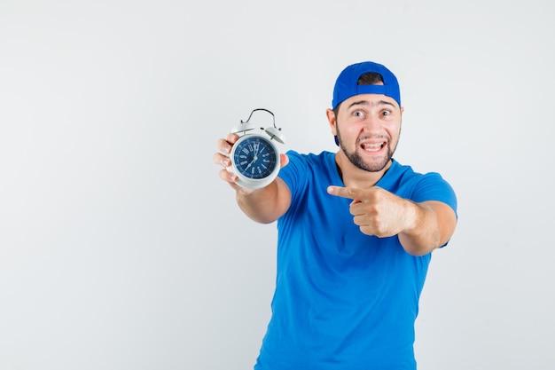 파란색 티셔츠와 모자에 알람 시계를 가리키고 긍정적 인 찾고 젊은 남자