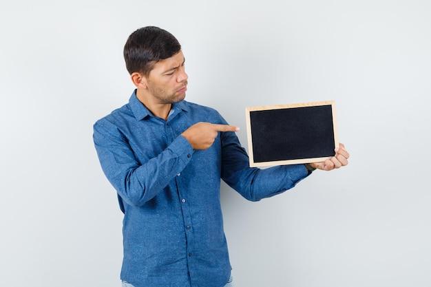 파란색 셔츠를 입은 칠판을 가리키며 초점을 맞춘 앞모습을 바라보는 청년.