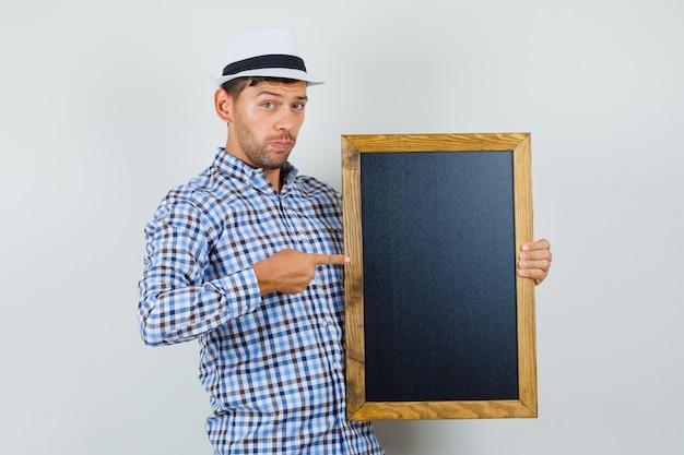 체크 셔츠에 칠판에서 가리키는 젊은 남자 무료 사진