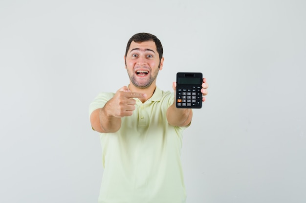 若い男がtシャツで電卓を指して、幸せそうに見える、正面図。