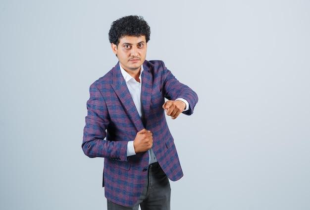 Молодой человек, указывая на камеру в рубашке, куртке, штанах и выглядит уверенно. передний план.