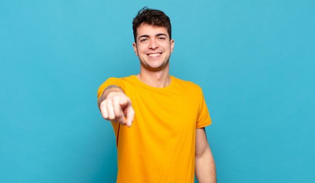 満足、自信を持って、フレンドリーな笑顔でカメラを指して、あなたを選ぶ若い男