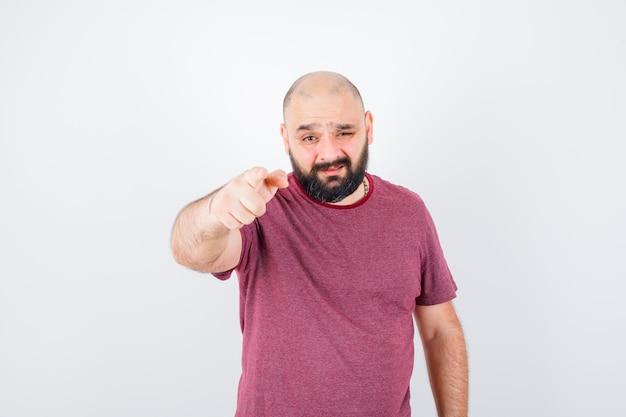 Молодой человек, указывая на камеру с указательным пальцем в розовой футболке и серьезный вид спереди.