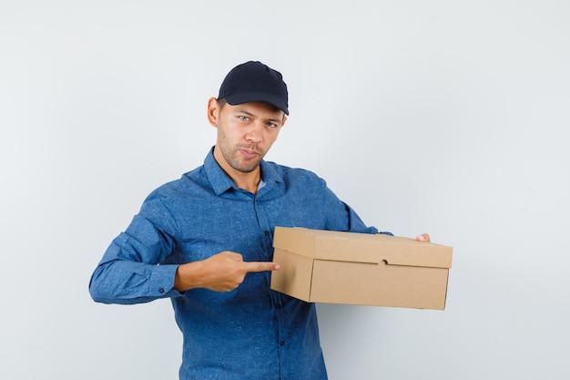 青いシャツ、キャップの段ボール箱を指して、自信を持って見える若い男。正面図。