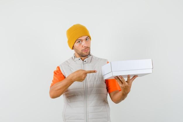 Tシャツ、ジャケット、帽子の正面図で段ボール箱を指している若い男。