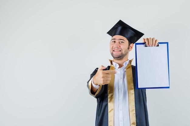 卒業式の制服を着たクリップボードを指差して自信を持って見ている若い男、正面図。