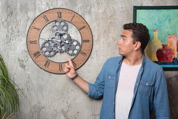 時計を指して、大理石の背景にポーズをとる若い男。高品質の写真