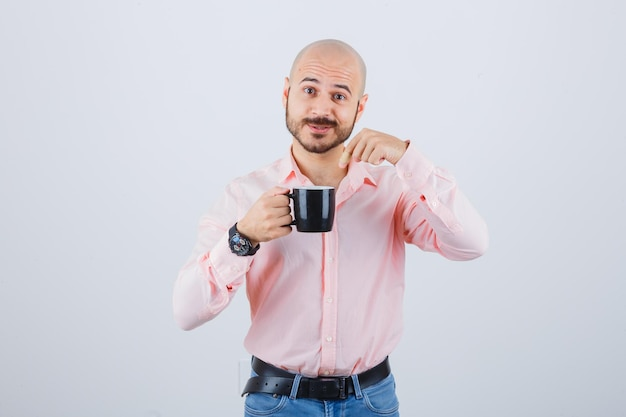 젊은 남자는 분홍색 셔츠, 청바지를 입은 컵을 가리키며 놀란 표정을 짓고 있습니다.
