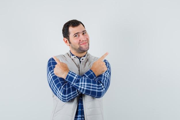 Молодой человек, указывая на разные стороны со скрещенными руками в рубашке, куртке без рукавов и благодарным взглядом, вид спереди.