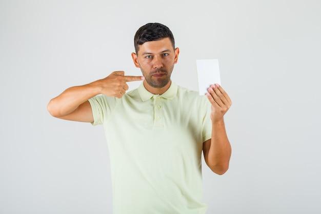 Молодой человек, указывая на пустую бумагу в футболке