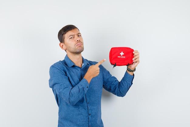 青いシャツを着た救急箱を指差して真面目な青年。正面図。