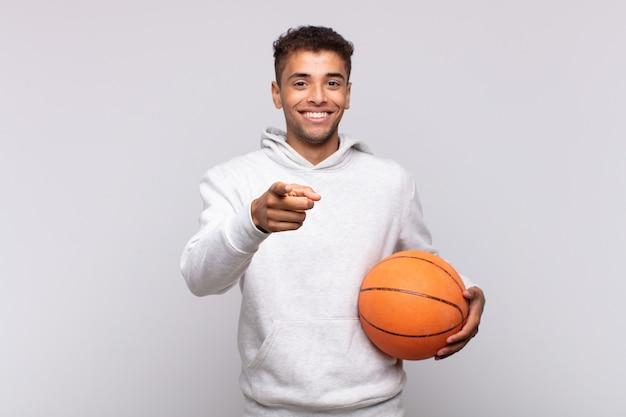 満足し、自信を持って、フレンドリーな笑顔で正面を指して、あなたを選んでいる若い男。バスケットコンセプト