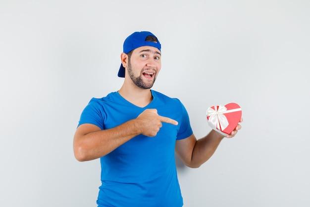 青いtシャツとキャップのギフトボックスを指して楽観的に見える若い男