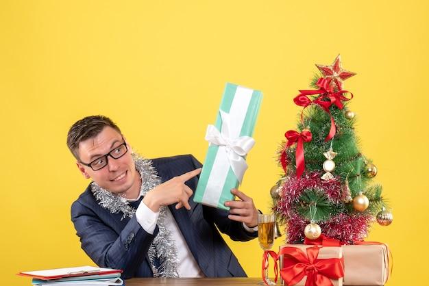 Молодой человек, указывая на подарок, сидит за столом возле елки и подарки на желтом