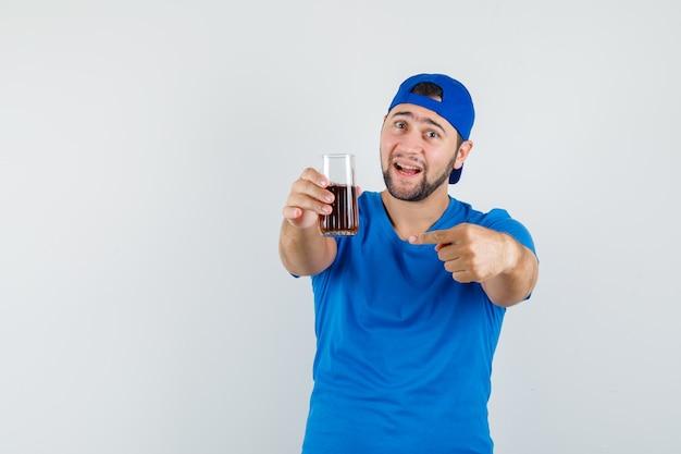 青いtシャツとキャップの飲み物のガラスを指して楽観的に見える若い男