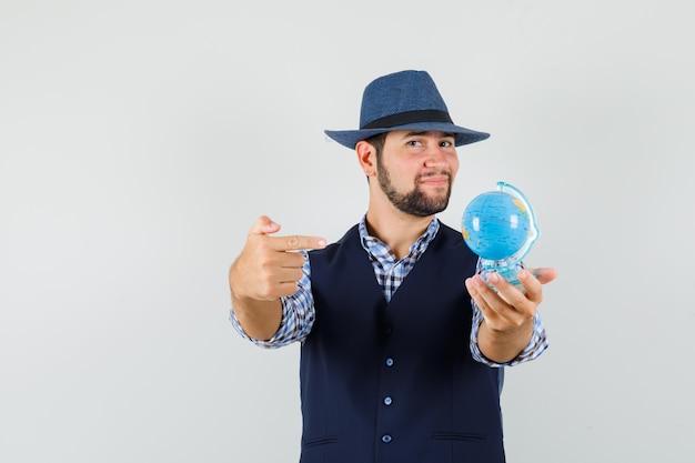 젊은 남자 셔츠, 조끼, 모자에 세계를 가리키고 자신감을 찾고. 전면보기.