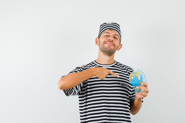 스트라이프 티셔츠 모자에 글로브 모델을 가리키고 쾌활한 찾고 젊은 남자