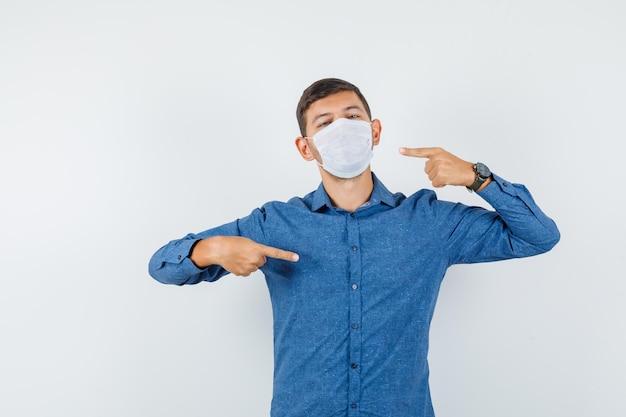 파란색 셔츠 전면 보기에서 자신과 마스크를 가리키는 젊은 남자.