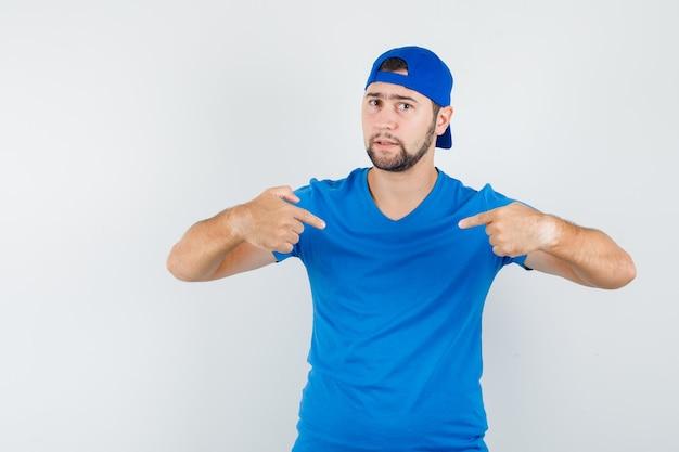 파란색 티셔츠와 모자에 자신을 가리키고 자신감을 찾고 젊은 남자