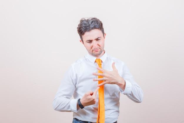 셔츠, 청바지에 그의 다섯 손가락을 가리키고 슬픈 찾고 젊은 남자