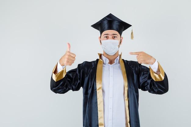 若い男は彼のマスクを指して、卒業生の制服、正面図で親指を示しています。