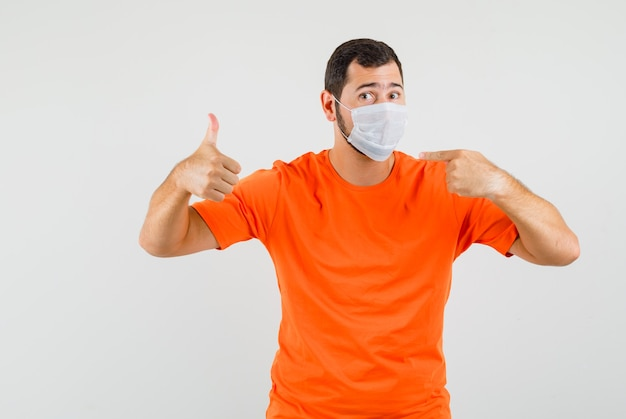 オレンジ色のtシャツの正面図で親指を上に向けて彼のマスクを指している若い男。