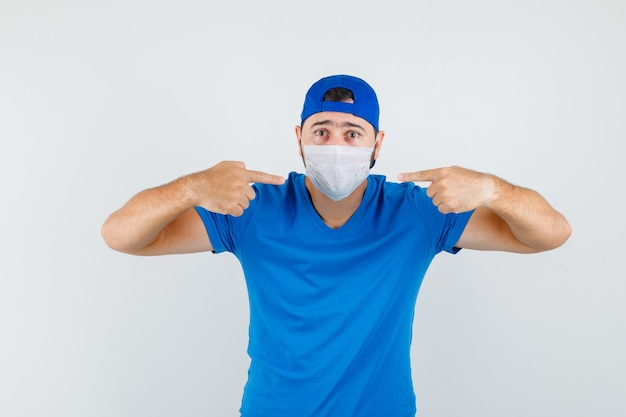 Молодой человек, указывая на свою медицинскую маску в синей футболке и кепке и внимательно глядя