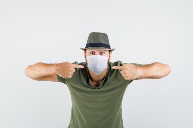 Молодой человек, указывая на свою медицинскую маску в зеленой футболке и шляпе