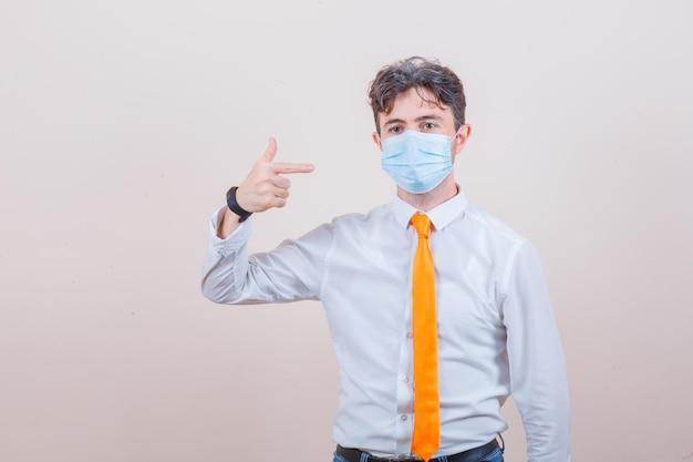 셔츠, 넥타이에 그의 의료 마스크를 가리키고 조심스럽게 찾고 젊은 남자