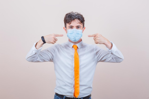 젊은 남자 셔츠, 넥타이, 청바지에 그의 의료 마스크를 가리키고 조심스럽게 찾고