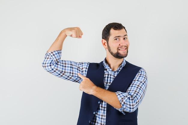若い男はシャツ、ベスト、自信を持って、正面図で彼の筋肉を指しています。