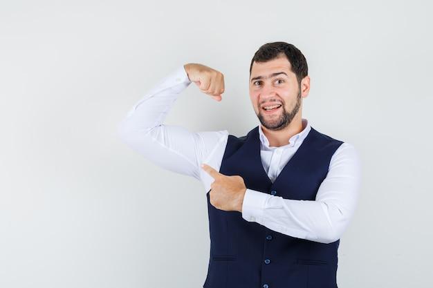 シャツ、ベスト、強く見える彼の筋肉を指している若い男