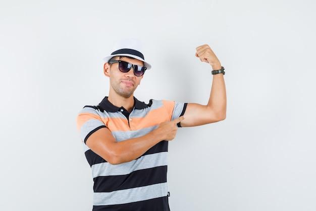 Tシャツと帽子で彼の筋肉を指して、強く見える若い男
